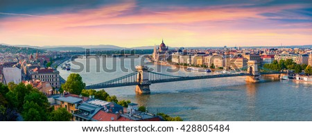 Panoramic cityscape of Hungarian parliament building with famous Chain Bridge on the Danube river. Colorful spring  sunset in Budapest, Hungary, Europe. Artistic style post processed photo.