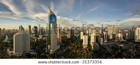 Panoramic cityscape of Indonesia capital city Jakarta at sunset. A rare clear day in the polluted city. - stock photo