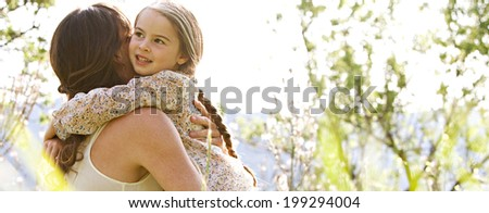 Panoramic close up portrait of a joyful mother and daughter relaxing together in a beautiful summer field, hugging and enjoying a sunny holiday outdoors. Family love and holiday activities lifestyle. - stock photo