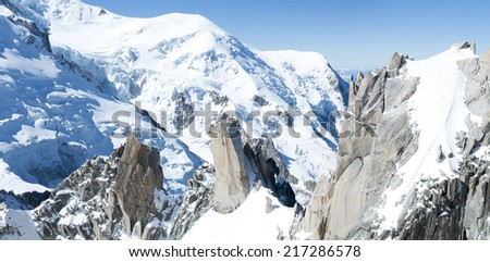 Panoramic composite of Mont Blanc mountain range, In Chamonix, France, with climbers on its rocks - stock photo