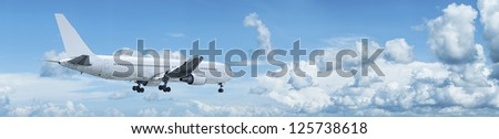 Panoramic composition of a jet with blank fuselage in a blue cloudy sky - stock photo