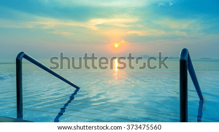 Panoramic dramatic view of Infinity Swimming pool with stair and beautiful sunset on the sea at twilight times - Vintage Filter - stock photo
