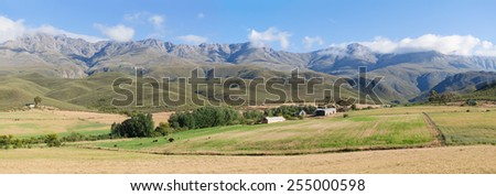 Panoramic farm landscape with high mountains and green fields - stock photo
