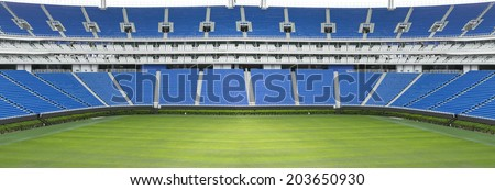 Panoramic football stadium with green grass and blue seats - stock photo