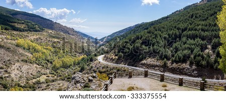 Panoramic high resolution image of the winding A337 road from the Puerto de la Ragua mountain pass over the Sierra Nevada mountains in Andalucia, Spain - stock photo