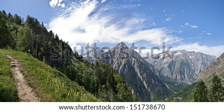 Panoramic image of an Alpine landscape, with a path leading to the mountains - stock photo