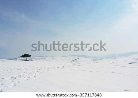 Panoramic image of beautiful, idyllic snowy winter landscape in the mountains, on a crisp, quiet, sunny morning. Snow covered hills and clear blue sky. - stock photo