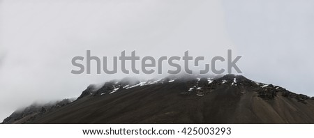 Panoramic image of mountain tops in low clouds