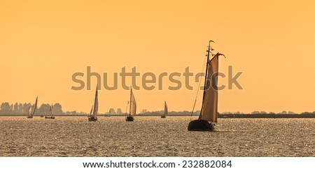 Panoramic image of traditional Frisian Dutch sailing ships during sundown - stock photo