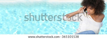 Panoramic image of young black female during spring break, near pool, using her phone.