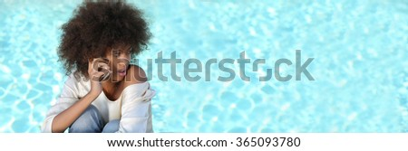 Panoramic image of young black woman near pool using her phone.