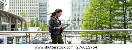 Panoramic image of young mixed race businesswoman portrait outdoors in Canary Wharf area in London working with tablet. - stock photo