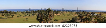 Panoramic landscape of a golf course on the coastline. - stock photo