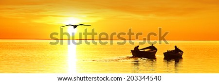 panoramic landscape of a sunset with fishermen - stock photo