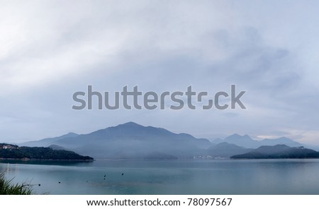 Panoramic landscape of lake with mountain under cloudy sky, famous attraction, Sun Moon Lake situated in Yuchi, Nantou, Taiwan, Asia. - stock photo