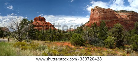 Panoramic landscape of Sedona canyons, Arizona with supeb clouds, typical desert vegetation, cactii and trees. No further description is necessary to convey that this is an Arizona landscape. - stock photo