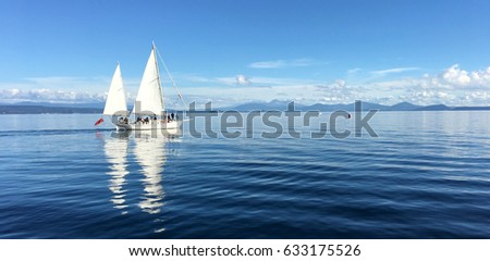 Panoramic landscape view of a white yacht sail boats sailing over Lake Taupo North Island New Zealand