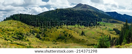 Panoramic landscape with low hills which are covered with forest - stock photo