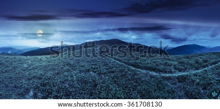 panoramic landscape with narrow meadow path in grass on top of mountain range at night in full moon light - stock photo