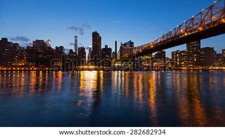 Panoramic midtown Manhattan skyline with reflections at night from Roosevelt island. New York City. - stock photo