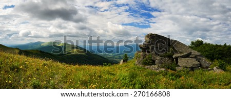 Panoramic mountains landscape with grassy hills and slopes and cloudy sky