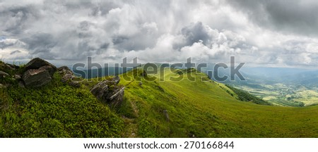 Panoramic mountains landscape with grassy hills and slopes and cloudy sky - stock photo