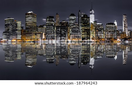 panoramic night view of New York City with reflection in water