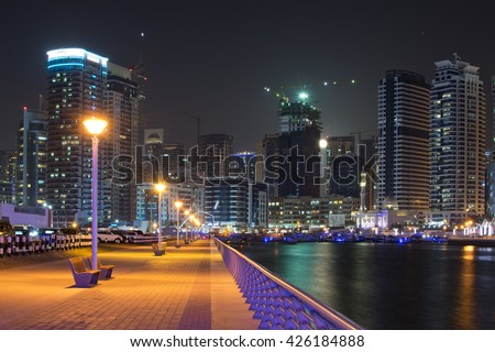 Panoramic night view with modern skyscrapers and water pier of Dubai Marina from the marina creek walk at night, United Arab Emirates - stock photo