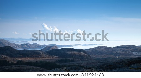 Panoramic Norwegian landscape with sea, sky and dark coastal mountains