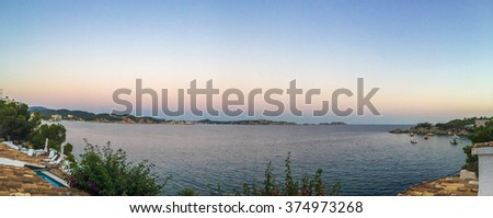 Panoramic ocean shoreline surrounded by trees, boathouse and boats with little town on the horizon at dusk - stock photo