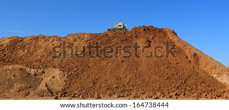 panoramic of a bulldozer at work on the top of the ground - stock photo