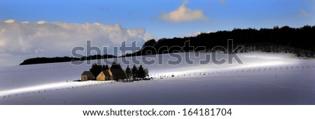 panoramic of a small barn in a snowy landscape - stock photo