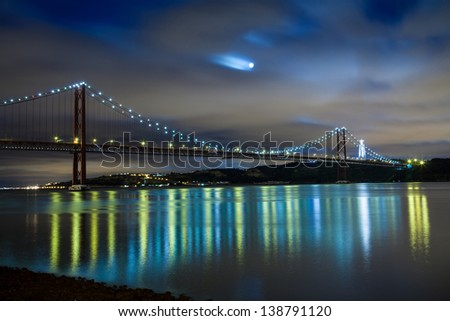 Panoramic of 25 de Abril bridge over Tagus river in Lisbon at night, Portugal - stock photo