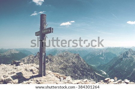 Panoramic of Summit Cross on Mountain Peek in Allgau Alps on Sunny Day with Blue Sky and View of Mountain Ranges in Distance, near Germany-Austria Border - stock photo