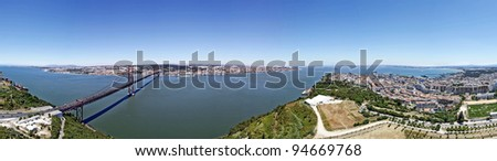 Panoramic over the city of lisbon where you can see the tagus river, the bridge, the other side of the river, big christmas tree, the downtown and the historical part of the city - stock photo
