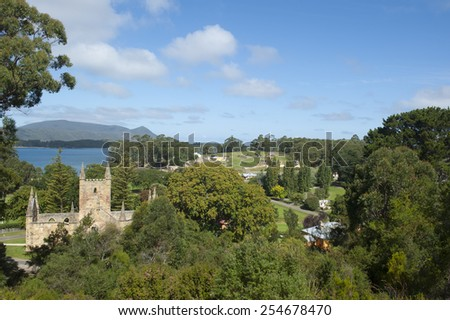 Panoramic overview of World Heritage Site Port Arthur Convict Settlement in Tasmania, Australia, with damaged church and other buildings and harbour in blurred background of park, copy space. - stock photo