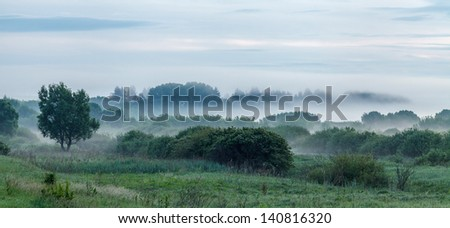 Panoramic photo of a morning fog in a valley - stock photo