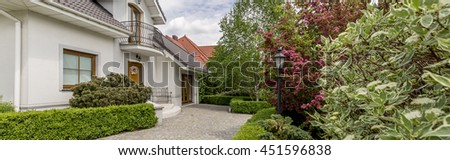 Panoramic photo of an elegant detached house with cobbled front yard and a vast well-groomed garden