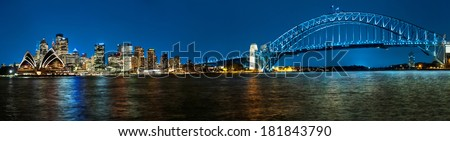 Panoramic photo of Sydney skyline with Harbour Bridge in the evening after sunset - stock photo