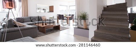 Panoramic photo of wooden staircase in modern living room - stock photo