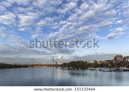 Panoramic photograph of Belgrade and Sava river with the New railroad bridge, made at dusk, from the lower tip of Ada Ciganlija river isle.  - stock photo