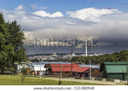 Panoramic photograph of Belgrade skyline, Sava river with the striking Bridge Over Ada pylon, and stormy afternoon skies, with rainy clouds approaching. - stock photo