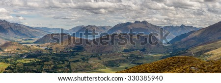 Panoramic photograph of Queenstown Lakes District in summer, Lake Wakatipu surrounded by mountains, cloudy skies. - stock photo