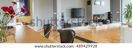 Panoramic picture of a cozy modern living room decorated with flowers