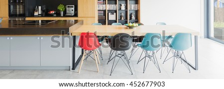 Panoramic picture of a modern kitchen with a big table