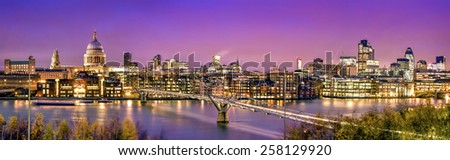 Panoramic picture of St. Paul's Cathedral, Millennium Bridge and  the Financial District at twilight. - stock photo