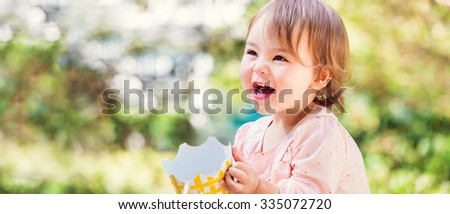 Panoramic portrait of a happy toddler girl with a big smile outside  - stock photo