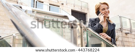 Panoramic portrait of a young beautiful business woman using a smart phone in stairs in financial city, speaking phone call conversation, outdoors. Professional using technology, smiling lifestyle. - stock photo