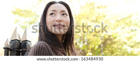 Panoramic portrait of an attractive Japanese tourist woman visiting the city of London during a sunny day and standing near a park with black railings, smiling and looking away, outdoors. - stock photo