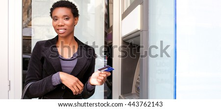Panoramic portrait of beautiful african american business woman smiling holding credit card at bank cash point in city, outdoors lifestyle. Smiling professional ethnic woman accessing funds in bank.